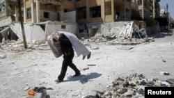 Сырыйскі паўстанец выносіць забітага таварыша з поля бою, Алепа, 16 жніўня 2012