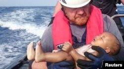 Німецький рятувальник-доброволець із тілом втонулої дитини-мігранта в Середземному морі неподалік берегів Лівії, фото 27 травня 2016 року