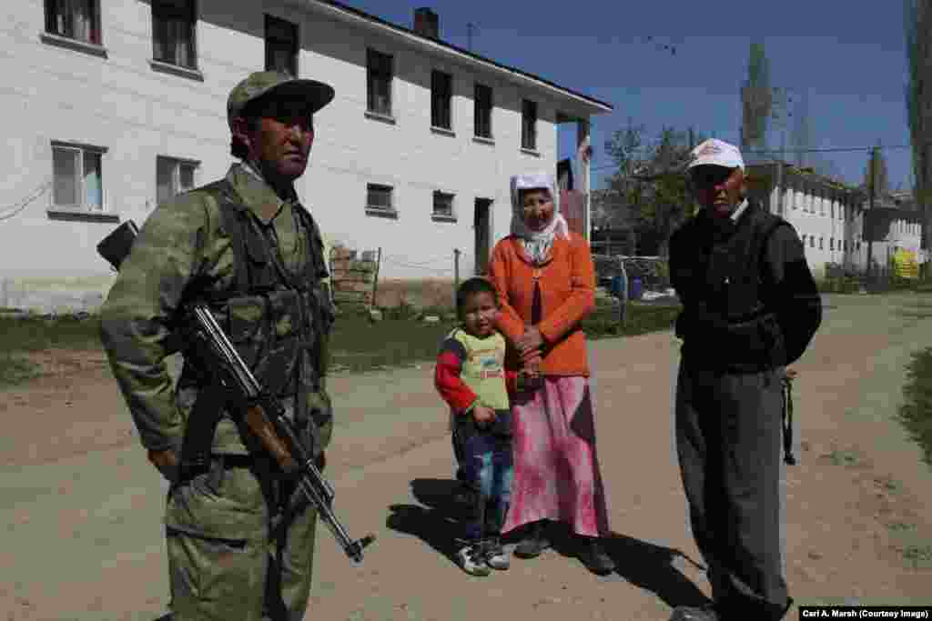 Mekhmet Turdu, a member of a local militia, with villagers. The Turkish government pays militia members to protect the Kyrgyz village from possible attacks by Kurdish militants who live in the region.