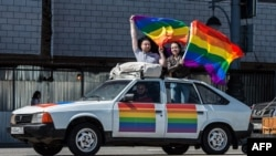 Gay-rights activists hold rainbow flags on top of a car during a protest in central Moscow on May 31.