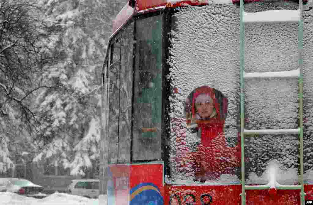 A commuter looks through a window of a tram in snowy Minsk. (AFP/Viktor Drachev)