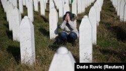 Жена се моли на гробот на убиените членови на нејзиното семејство во Меморијалниот центар Поточари во близина на Сребреница