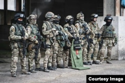 """A photo from Sato's collection showing a group of fellow airsoft enthusiasts in Russian FSB Alpha Group uniforms. There is a replica of an """"assault shield"""" used by the FSB's special forces (center right)."""