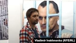 Антон Наумлюк на фоне фотографии Николая Карпюка