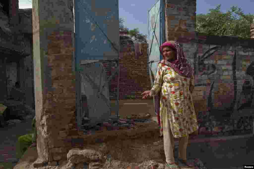 A Pakistani villager in Dhamala Hakimwalastands in the doorway of a house that was damaged in a recent exchange of fire with India.