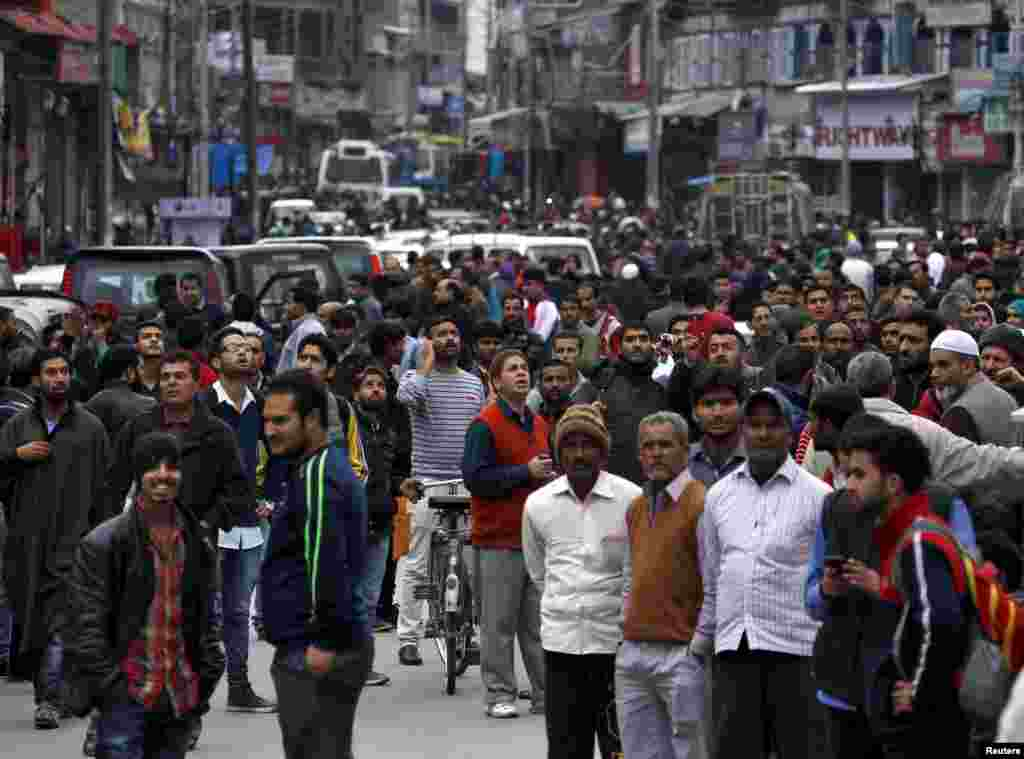 People stand on a road after vacating buildings in Srinagar.
