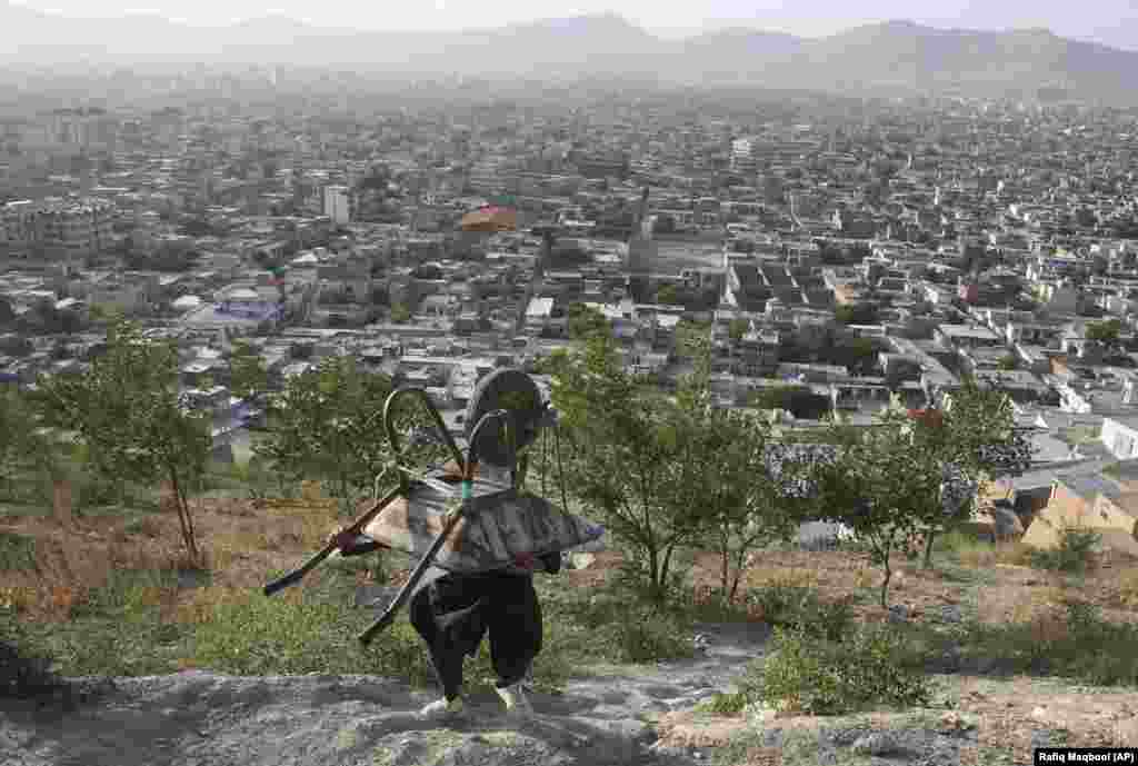 An Afghan boy carries his wheelbarrow in the mountains above Kabul. (AP/Rafiq Maqbool)