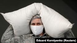 Radnik sa zaštitnom maskom nosi vreću brašna u gradu Nevinomisku, Rusija, 27. mart, 2020.