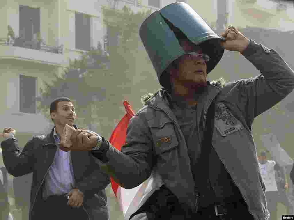 A protester throws a rock near Tahrir Square on the 10th day of demonstrations.