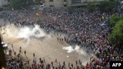 """Сторонники """"Братьев-мусульман"""" разбегаются от газовых шашек во время столкновений с полицией в Каире, 6 октября 2013 года."""