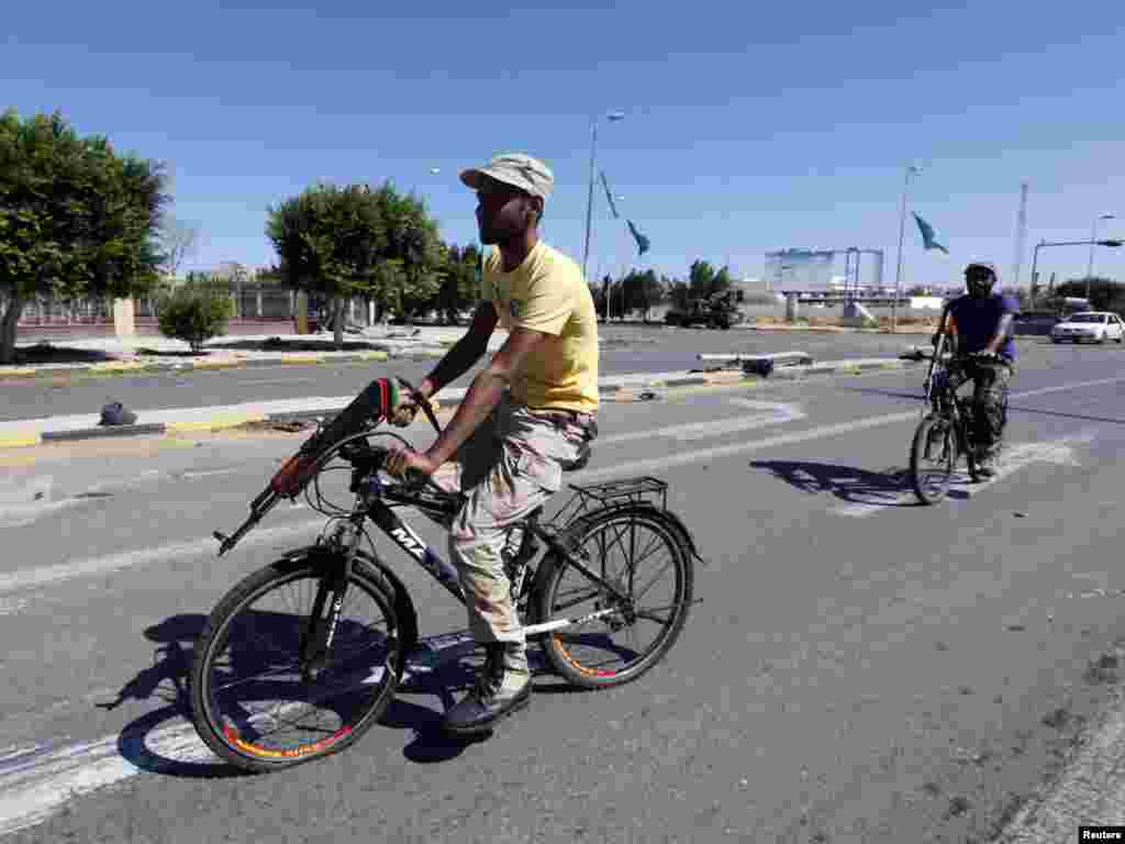 NTC fighters ride on bicycles to get to the front line in the center of Sirte, Libya. (Photo by Saad Shalash for Reuters)