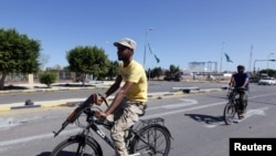 Libyan National Transitional Council fighters ride on bicycles to get to the front line in the center of Sirte on October 12.