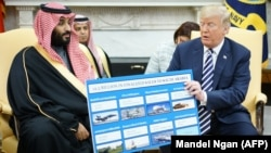 U.S. President Donald Trump (right) holds a defense sales chart with Saudi Arabia's Crown Prince Mohammed bin Salman in the White House on March 20.