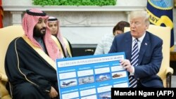 U.S. -- U.S. President Donald Trump (R) holds a defence sales chart with Saudi Arabia's Crown Prince Mohammed bin Salman in the Oval Office of the White House in Washington, March 20, 2018