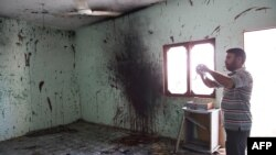 A man takes pictures in a room where a suicide blew himself up in Karachi on September 20.