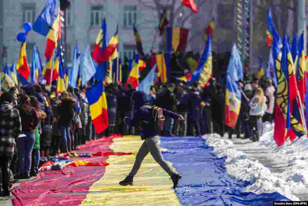 A girl jumps across a large Romanian flag during a rally ahead of the 100th anniversary of the unification of Bessarabia and Romania in central Chisinau, Moldova, on March 25. (EPA-EFE/Dumitru Doru)