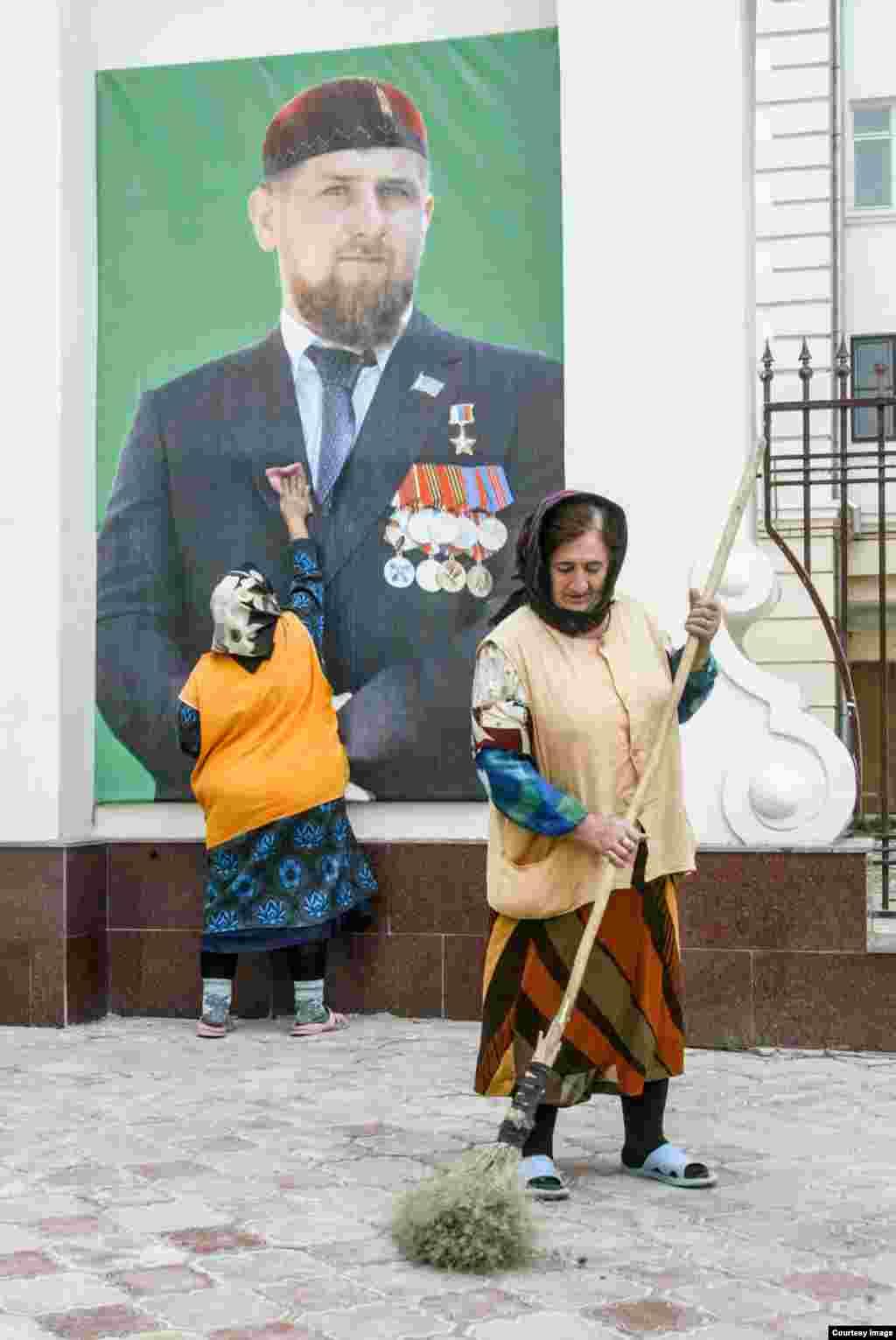 Женщина протирает фотографию Рамзана Кадырова.