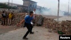 Египеттің бұрынғы президенті Мұхаммед Мурсиді қолдайтындар полицияға тас лақтырып қарсылық танытып жатыр. Наср, 27 шілде 2013 жыл.