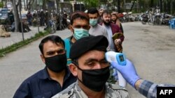 A health worker checks the body temperature of worshippers as a preventive measure against the COVID-19 before the Friday prayers on the first day of the Muslim holy month of Ramadan at Wazir Akbar Khan mosque in Kabul on April 24.