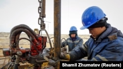 Workers in Kazakhstan do maintenance on an oil well. Low oil prices have brought sluggish growth and recession to the Caucasus and Central Asian economies.
