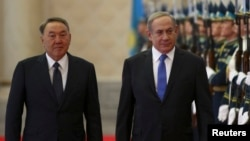 Kazakh President Nursultan Nazarbaev (left) and Israeli Prime Minister Benjamin Netanyahu review a guard of honor during a welcoming ceremony for the latter in Astana on December 14.