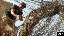 عامل يربط أسلاك توزيع الكهرباء من مولدة أهلية