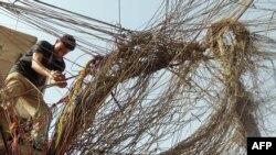 عامل عراقي يرتب أسلاك توزيع الكهرباء من مولدة كهربائية في محلة ببغداد