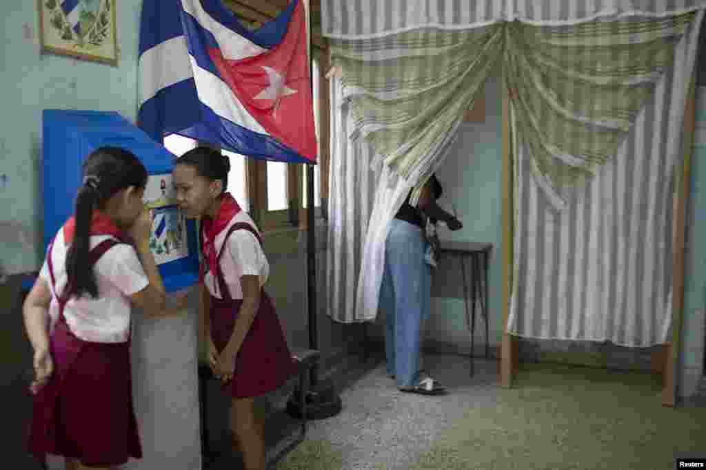 Ten-year-old schoolgirls Claudia Fuentes (right) and Laura Gonzales chat as an elector casts her vote at a polling station in Havana. Municipal elections took place in Cuba on April 19. (Reuters/Alexandre Meneghini)