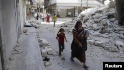 Syria -- Civilians walk near a destroyed building after a Syrian Air Force fighter jet launched a bomb in the city of Aleppo, 03Sep2012