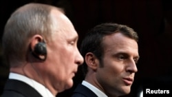 French President Emmanuel Macron (right) and Russian President Vladimir Putin give a joint press conference in Versailles in May.