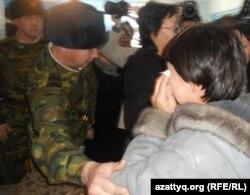 Военнослужащие просят плачущую родственницу одного из осужденных по обвинению в терроризме выйти из зала суда. Актобе, 14 декабря 2011 года.