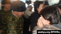 Военнослужащие просят плачущую родственницу одного из привлекаемых по обвинению в терроризме покинуть зал суда. Актобе, 14 декабря 2011 года.