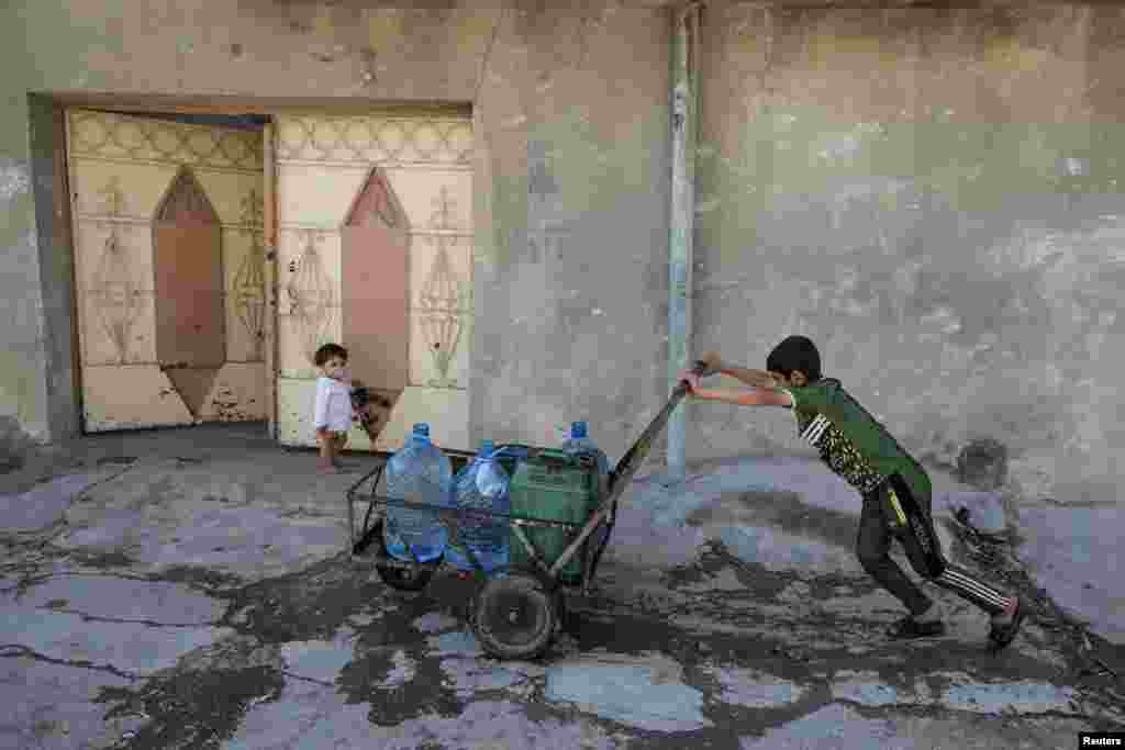 An Iraqi boy pushes water containers along a street in eastern Mosul. (Reuters/Marko Djurica)