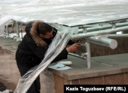 «Алмалы» метро бекетіне кіре берісте жұмыс істеп жатқан ер адам. Алматы, 12 желтоқсан 2011 ж.