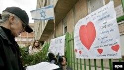 Женщина читает молитву о здоровье премьер-министра Израиля Ариэля Шарона около госпиталя Hadassah в Иерусасиме.