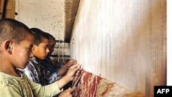 Afghan boys work on a carpet in Kabul.