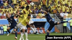 Players are shown in a match between the Colombian and Japanese soccer teams at the World Cup.