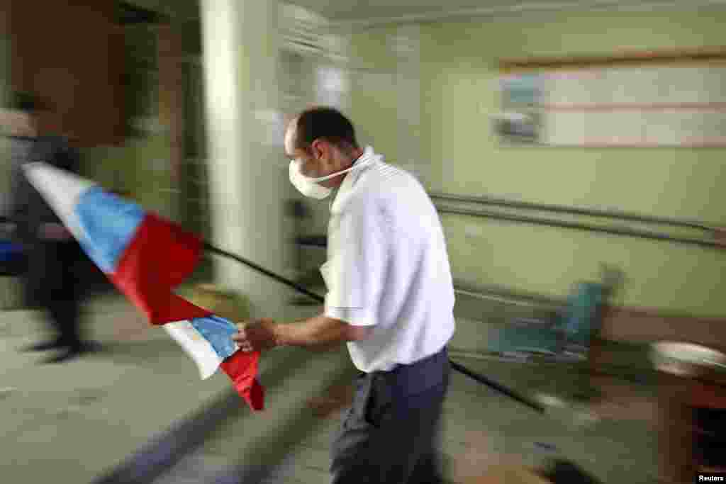 A pro-Russia rebel carries a Russian flag into the city hall in Mariupol, eastern Ukraine. (Reuters/Marko Djurica)
