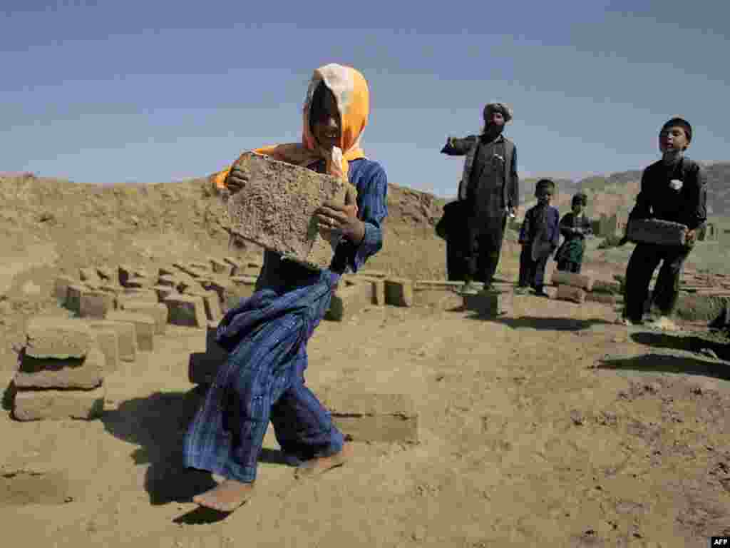 Internally displaced children work in a brick factory in the western Afghan city of Herat.