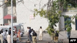 Police and rescue workers attend to victims of the suicide bombings near Islamabad.