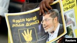 """""""Мұсылман бауырлар"""" қозғалысының жақтаушысы наразылық акциясында Мұхаммед Мурсидің суретін ұстап жүр. Каир, 6 қыркүйек 2013 жыл."""