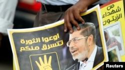Një proitestues e mbanë fotografinë e Morsit gjatë demonstratës së sotme në Kajro