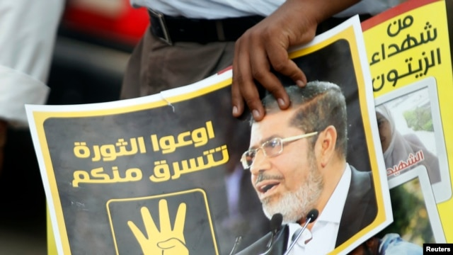 A member of the Muslim Brotherhood holds a poster of ousted Islamist leader Muhammad Morsi.