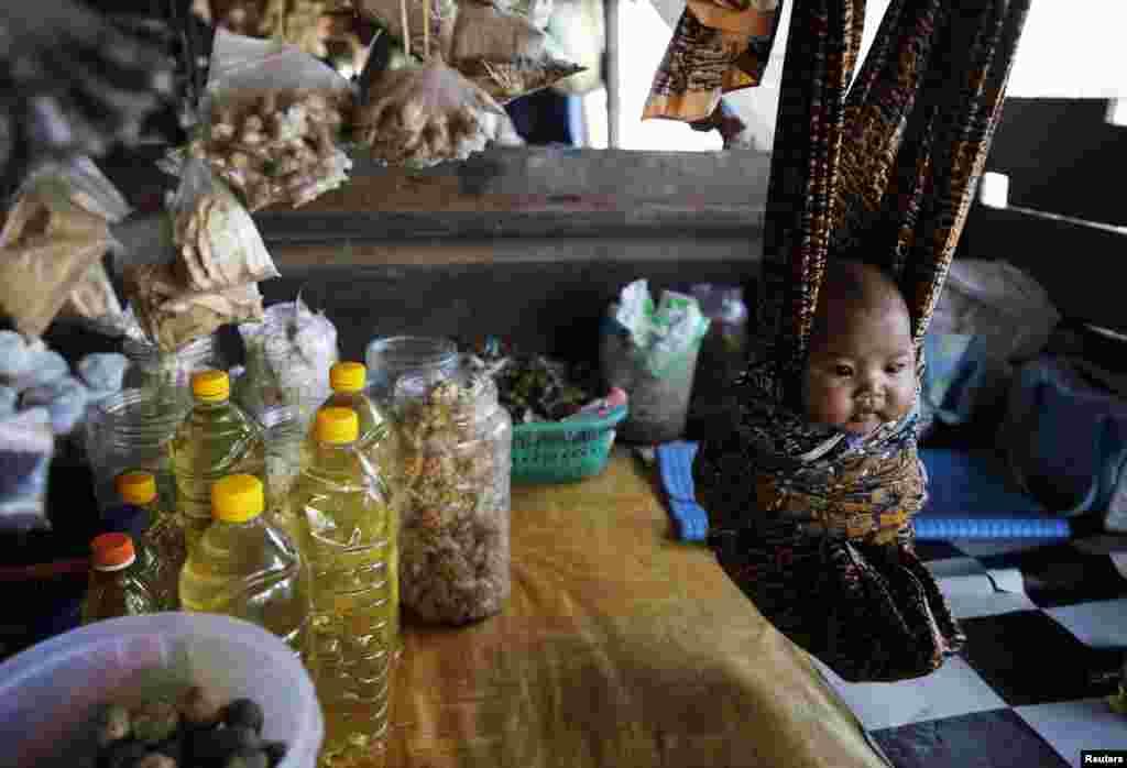 Dok majka prodaje robu, dijete je na sigurnom - u krpenoj visećoj mreži. Prizor sa pijace u Pangkalan Bun, Indonezija. (Reuters/Beawiharta)