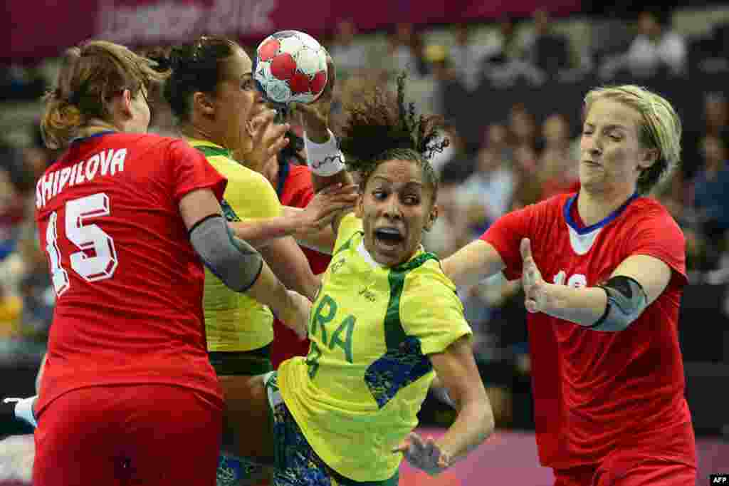 Brazil's centreback Ana Paula Rodrigues (center) vies with Russian players during a women's preliminary Group A handball match at the London Olympics. (AFP/Javier Soriano)