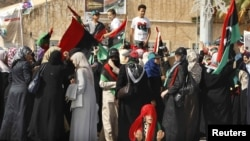 Ливиялық әйел Каддафидің өмірден өткеніне басқалармен бірге қуанышын білдіріп жатыр.