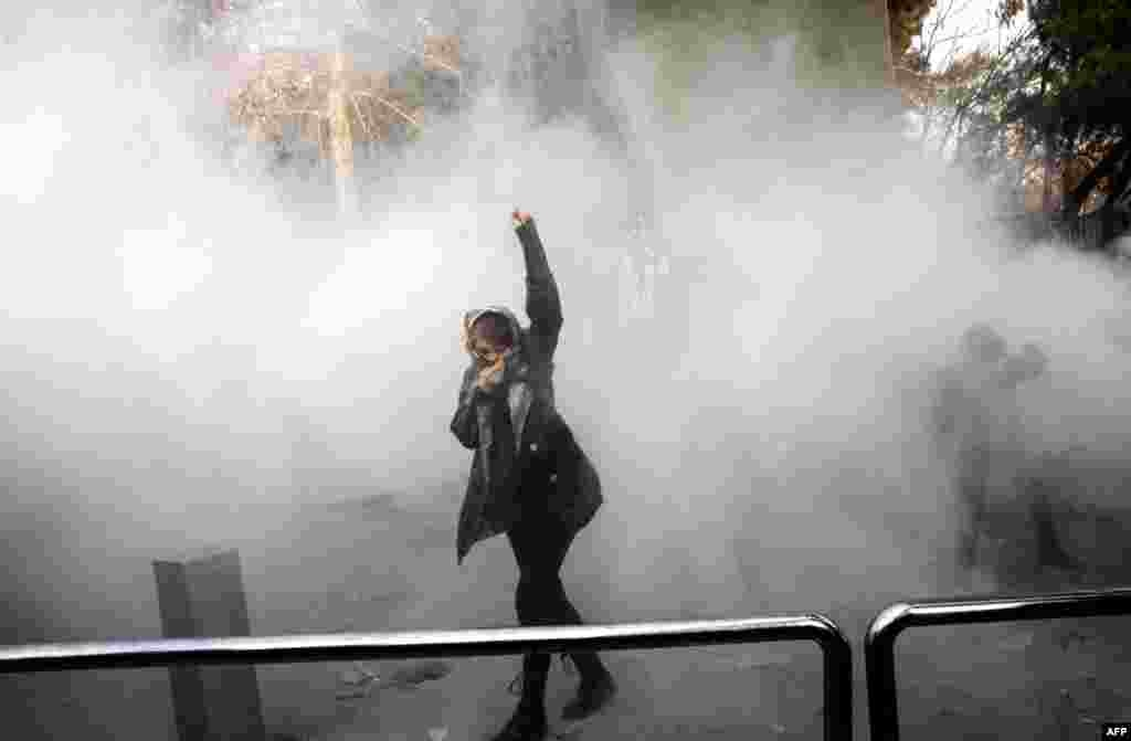 An Iranian woman raises her fist amid the smoke of tear gas during a protest at Tehran University on December 30. (AFP)