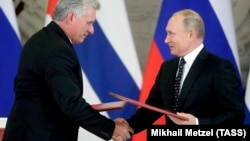 Russian President Vladimir Putin (right) and Cuban President Miguel Diaz-Canel exchange documents following their meeting at the Kremlin in Moscow on November 2.