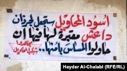 """لافتة كتبت فوق شعارات ممسوحة لـ""""داعش"""""""