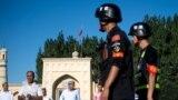 Қашғар қаласында мешіттен шығып келе жатқан мұсылмандар және Қытай полициясы. Шыңжаң Ұйғыр автономиясы, Қытай, 26 маусым 2017 жыл.